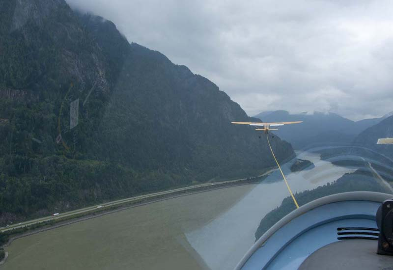 Glider being towed by Cessna, over the Fraser River, Hope, BC