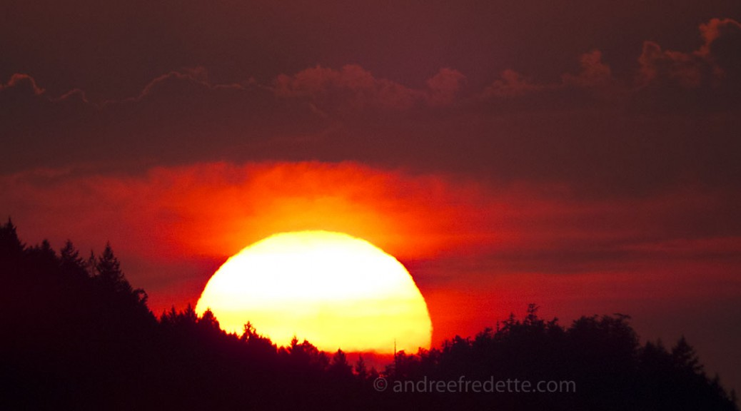 The sun, cradled by two hills on North Pender Island. August 12, 2015. Photo by Andrée Fredette