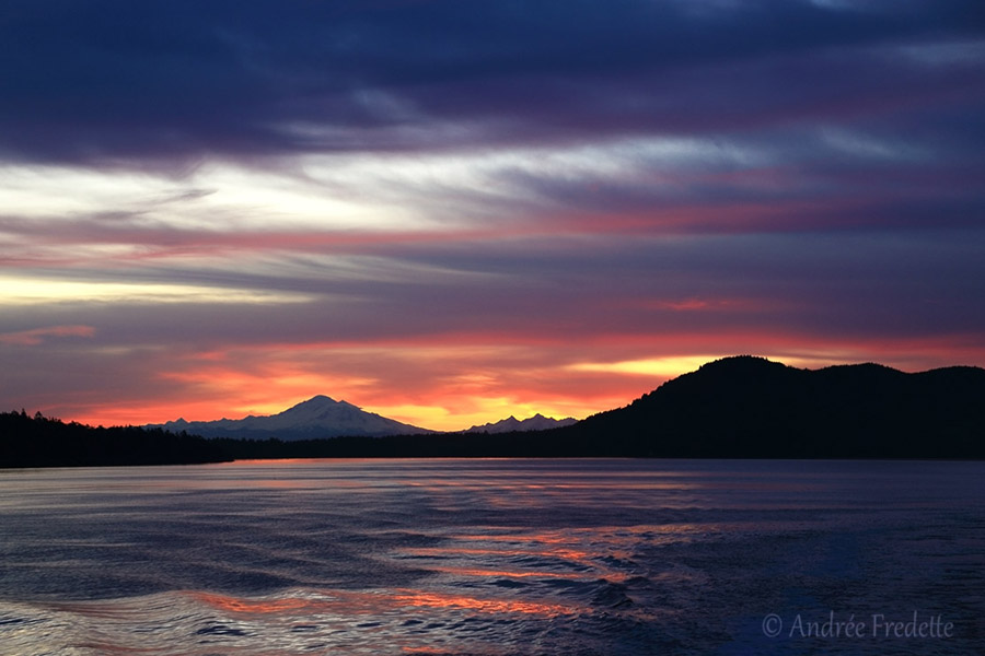 Ferry sunrise, with the silhouettes of Mt Baker on the left, and Saturna Island on the right. Photo by Andrée Fredette